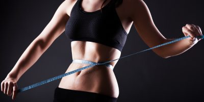 Fitness woman wet belly after exercise measuring her waist, weight loss concept