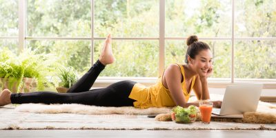 woman-lying-down-with-healthy-food-in-workout-clothes